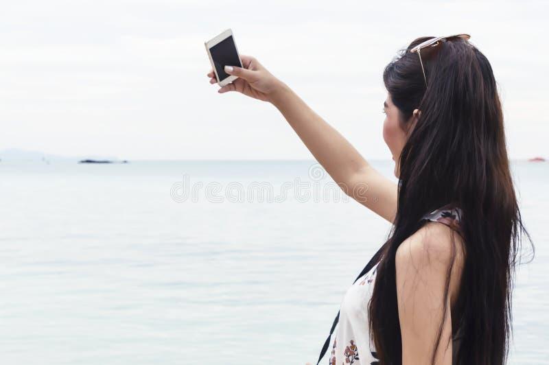 Belle jeune femme prenant la photo sur la plage Mode de vie heureux d'île images stock