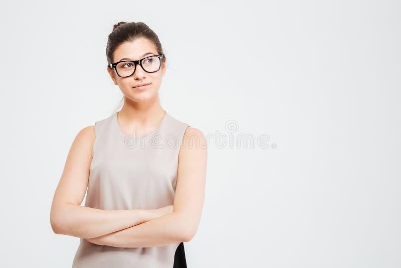 Belle jeune femme réfléchie d'affaires se tenant avec des bras croisés photo libre de droits
