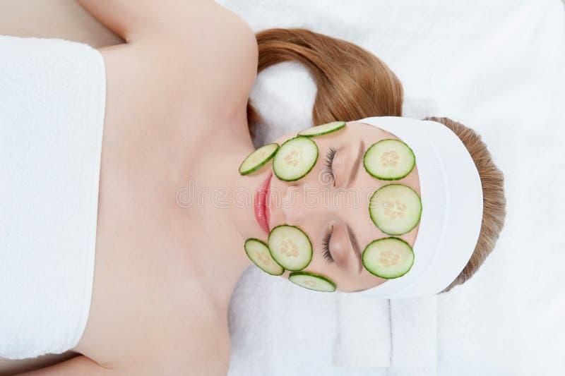 Belle jeune femme recevant le masque facial de photo stock