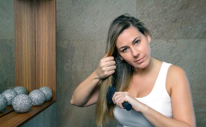 Belle jeune femme redressant des cheveux avec a photo libre de droits