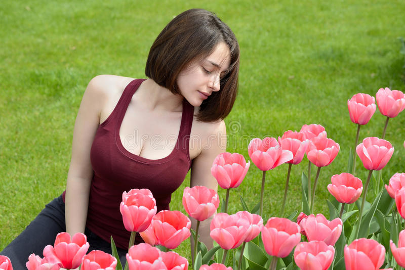 Belle jeune femme regardant le jardin rose de tulipe photographie stock libre de droits