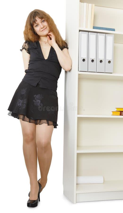 Belle jeune femme restant les étagères proches de bureau image stock