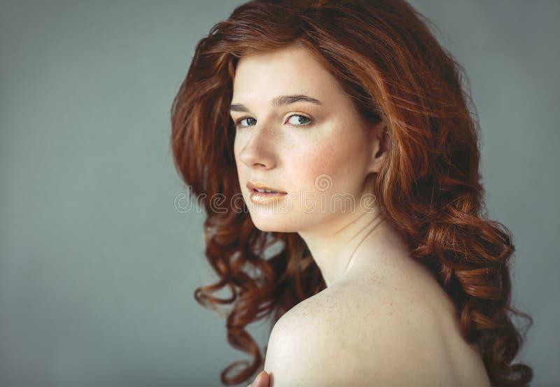 Belle jeune femme rousse avec le portrait de taches de rousseur image stock
