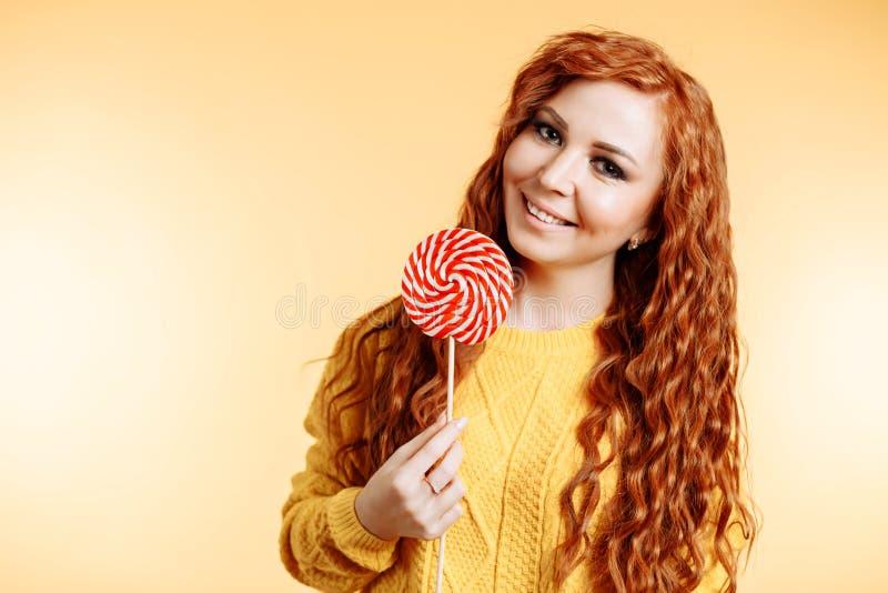 Belle jeune femme rousse bouclée tenant une lucette et un sourire blancs rouges photographie stock