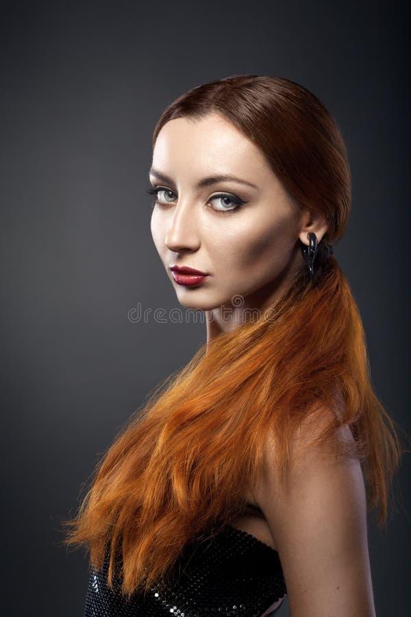 Belle jeune femme rousse d'isolement sur l'obscurité photographie stock