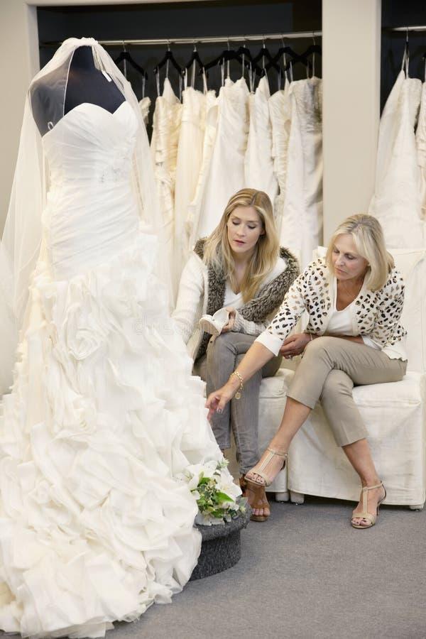 Belle jeune femme s'asseyant avec la mère tout en regardant la robe de mariage dans le magasin nuptiale photo libre de droits