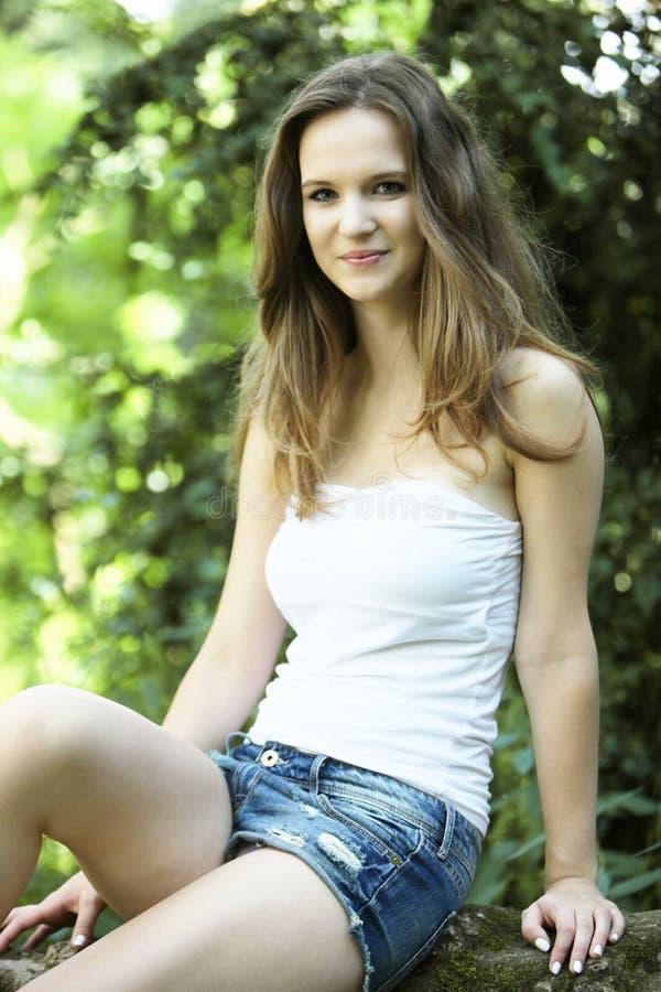 Belle jeune femme s'asseyant dans le jardin photo stock