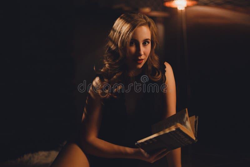 Belle jeune femme s'asseyant dans une lingerie noire et regardant in camera image stock