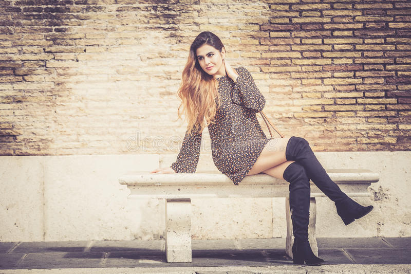 Belle jeune femme s'asseyant dehors sur un banc À la mode et sensuel photographie stock libre de droits