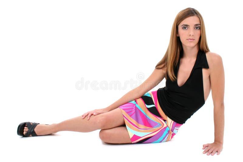 Belle jeune femme s'asseyant sur l'étage dans la robe d'été images stock