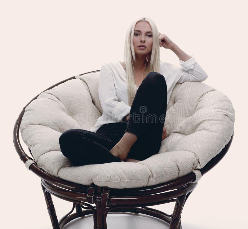 Belle jeune femme s'asseyant sur le divan dans un grand comfortabl photographie stock