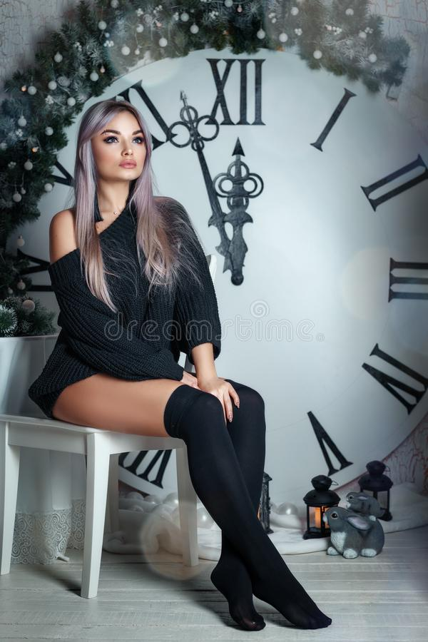 Belle jeune femme s'asseyant sur le fond d'un grand décor de Noël d'horloge, tenant une lampe-torche, attendant les vacances images libres de droits