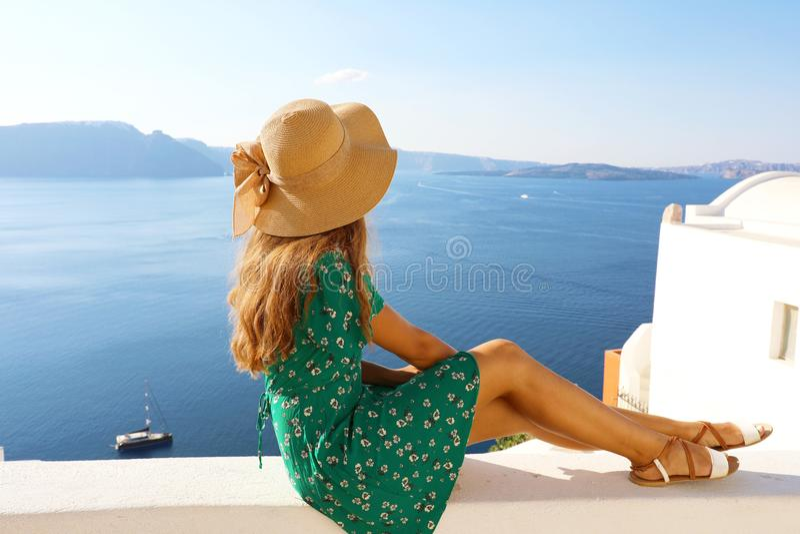 Belle jeune femme s'asseyant sur le mur regardant la vue renversante de la mer Méditerranée et de la caldeira dans Santorini, Grè photo stock