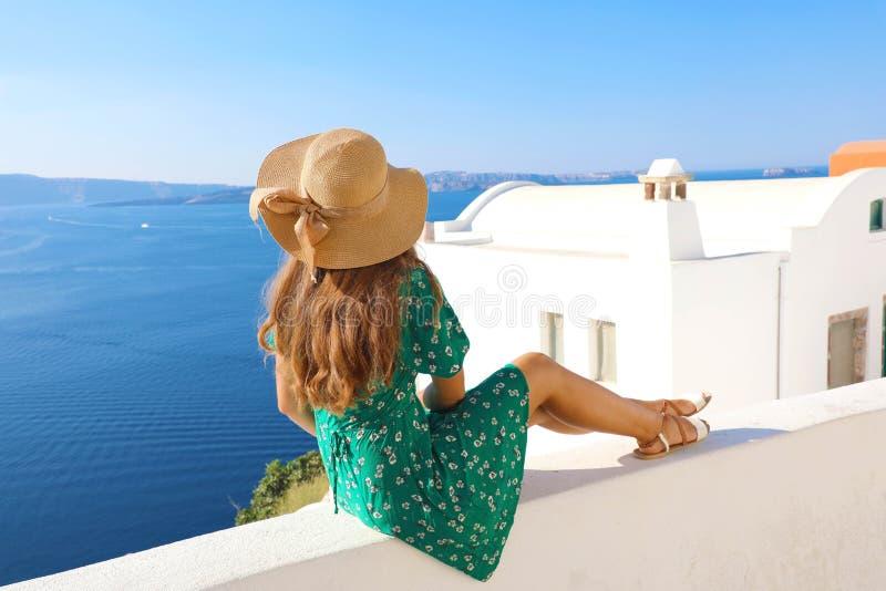 Belle jeune femme s'asseyant sur le mur regardant la vue renversante de la mer Méditerranée et du village de Santorini, Grèce, l' photo stock