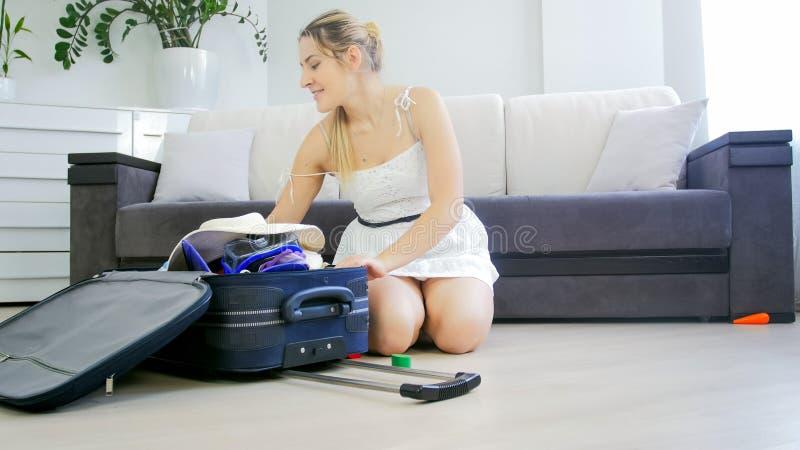 Belle jeune femme s'asseyant sur le plancher et les choses de emballage pour des vacances d'été photo libre de droits
