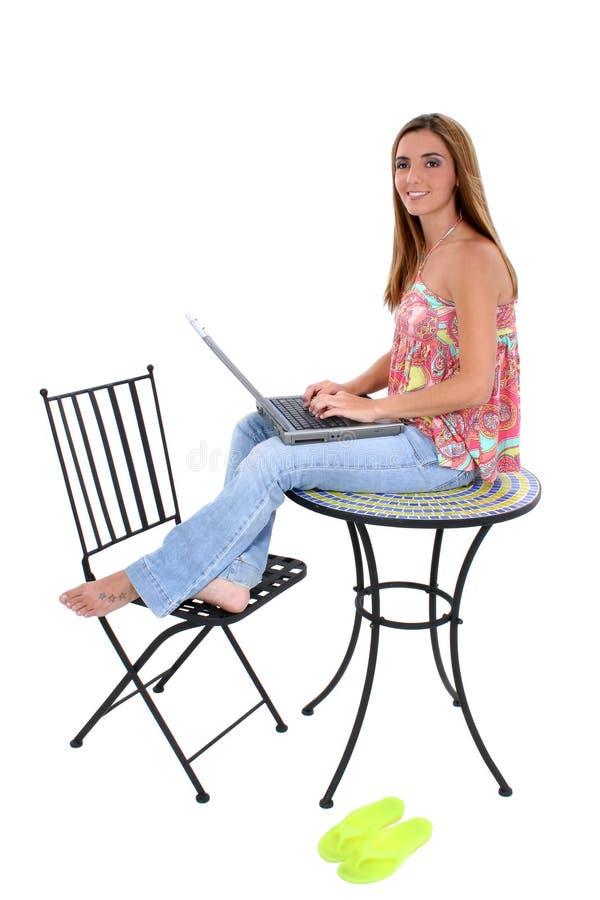 Belle jeune femme s'asseyant sur le Tableau travaillant sur l'ordinateur portatif photographie stock