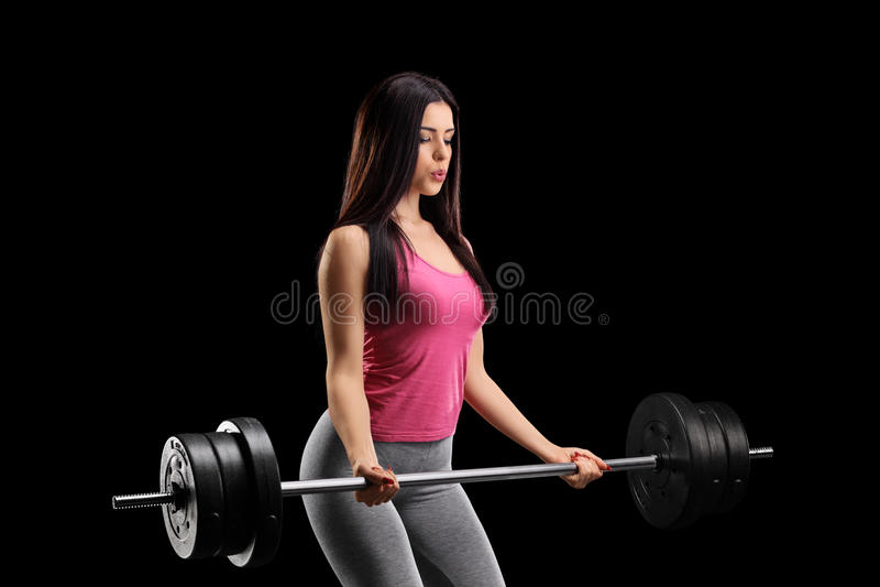 Belle jeune femme s'exerçant avec un barbell photo stock