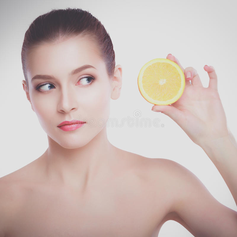 Belle jeune femme sans chemise tenant le morceau d'orange devant son oeil tout en se tenant sur le fond blanc image stock