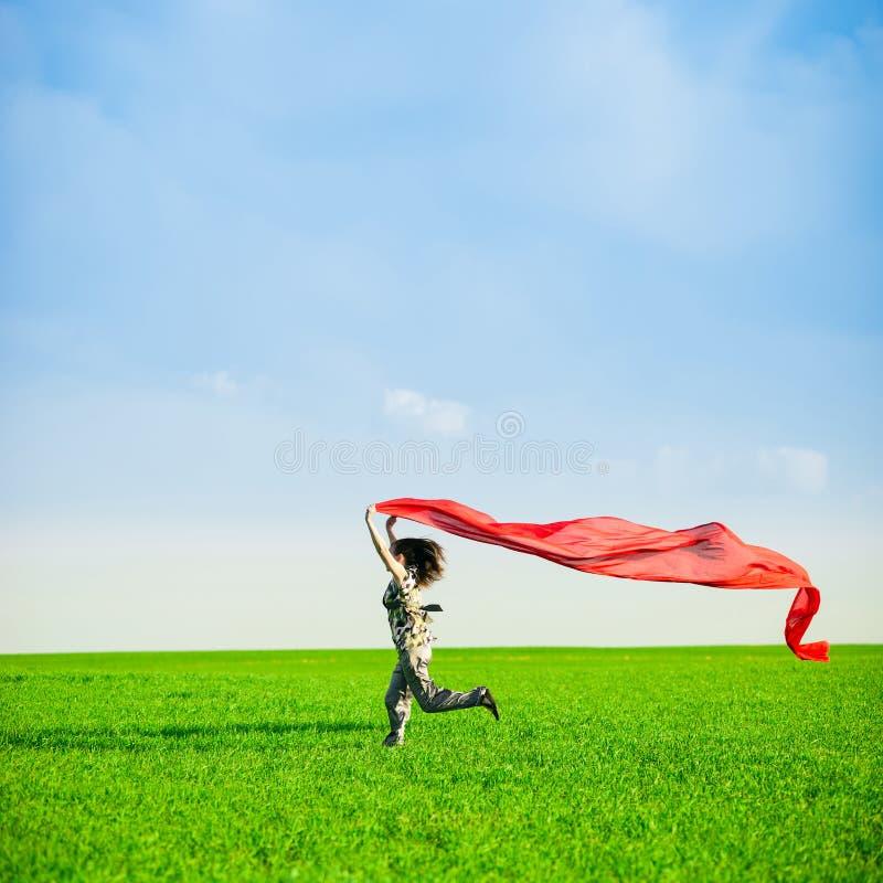 Belle jeune femme sautant sur un pré vert avec le tissu coloré photo libre de droits