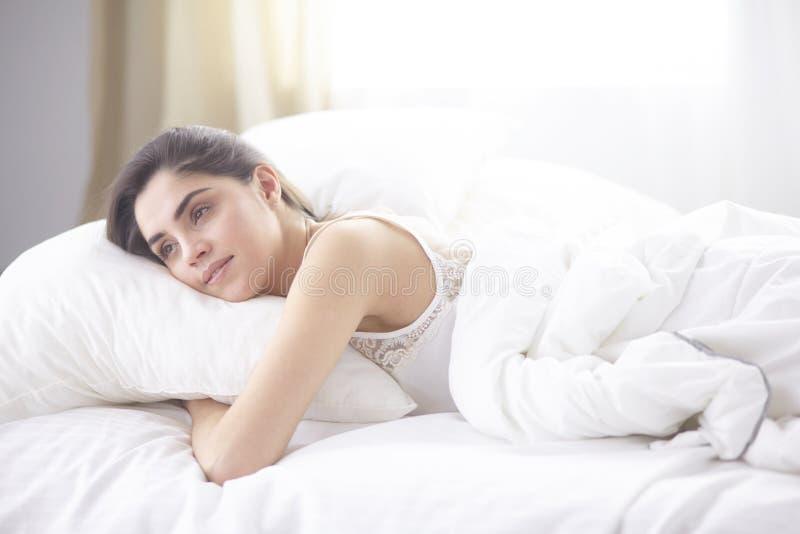 Belle jeune femme se dorant dans le lit pendant le matin Le beau visage modèle semble sexy in camera photo libre de droits