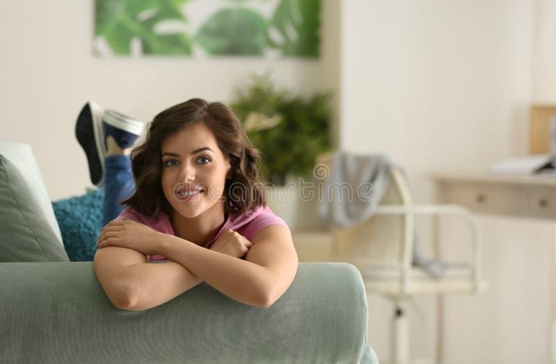 Belle jeune femme se reposant sur le sofa ? la maison photos libres de droits
