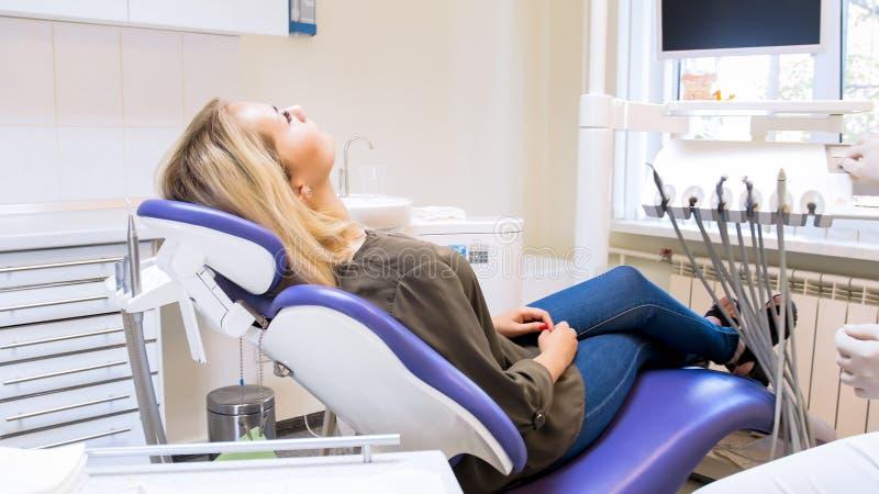 Belle jeune femme se situant dans la chaise de dentiste et le docteur de attente photos stock