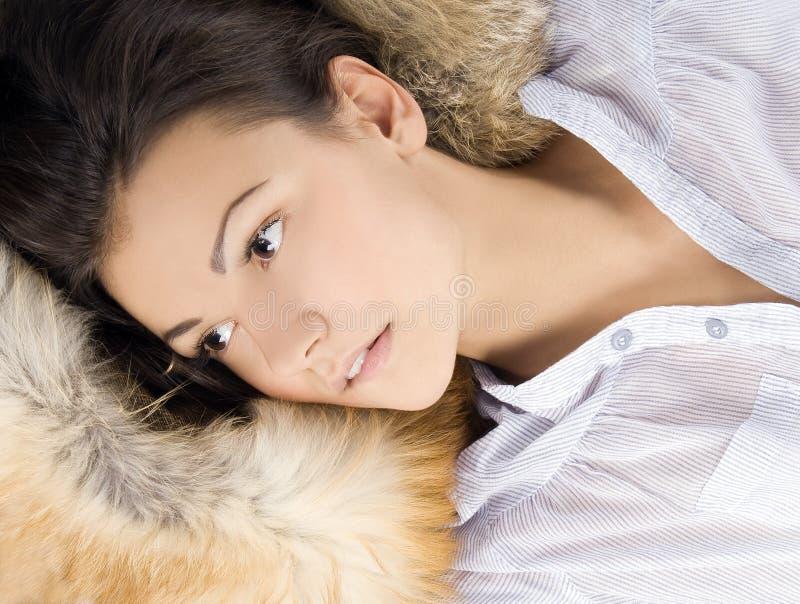 Belle jeune femme se situant dans une fourrure photographie stock libre de droits