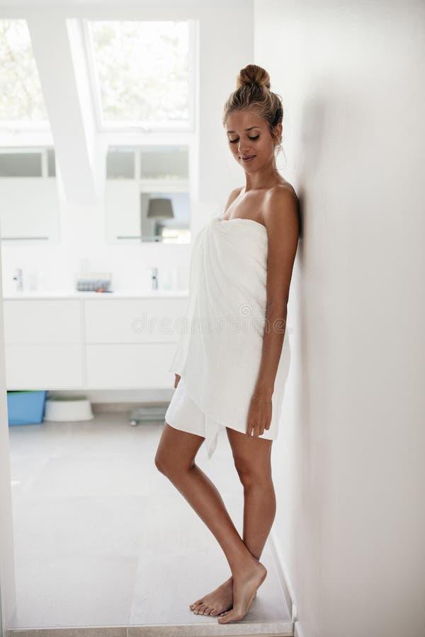 Belle jeune femme se tenant dans la salle de bains photos libres de droits