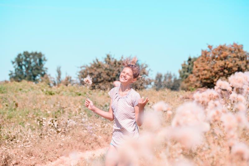 Belle jeune femme se trouvant sur le champ en herbe verte et pissenlit de soufflement outdoors Appréciez la nature Fille de souri photos libres de droits