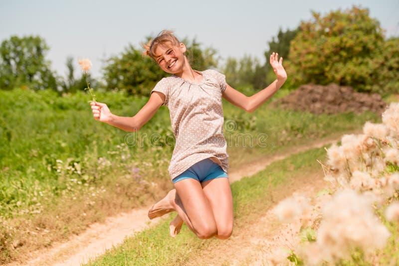 Belle jeune femme se trouvant sur le champ en herbe verte et pissenlit de soufflement outdoors Appréciez la nature Fille de souri images stock