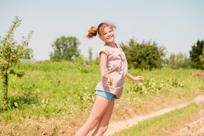 Belle jeune femme se trouvant sur le champ en herbe verte et pissenlit de soufflement outdoors Appréciez la nature Fille de souri photos stock