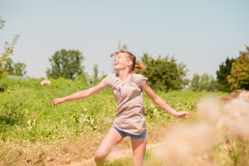 Belle jeune femme se trouvant sur le champ en herbe verte et pissenlit de soufflement outdoors Appréciez la nature Fille de souri image libre de droits