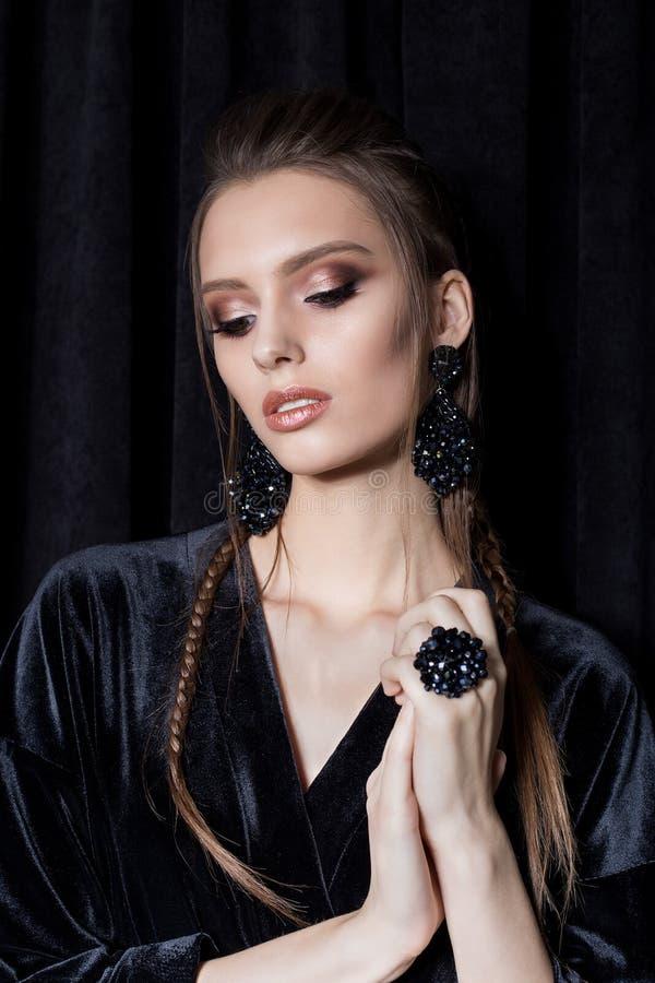 Belle jeune femme sexy avec les cheveux foncés tressés avec les boucles d'oreille lumineuses de bizhuterieyker de maquillage et d photographie stock