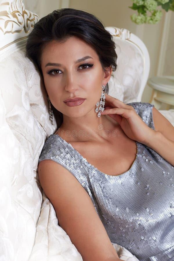 Belle jeune femme sexy de brune avec chic de maquillage de soirée toilettée portant une robe courte de soirée brodée avec de l'ar photographie stock libre de droits