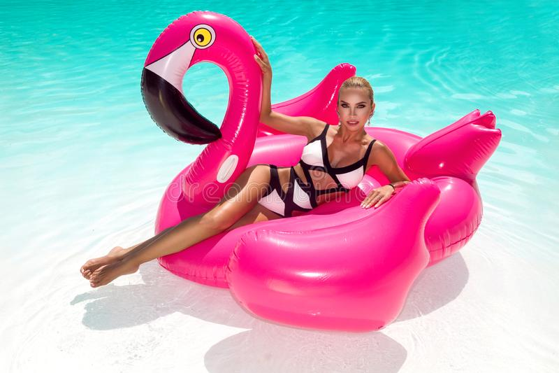 Belle jeune femme sexy et étonnante dans une piscine se reposant sur un flamboyant rose gonflable et riant, corps bronzé, longs c images stock