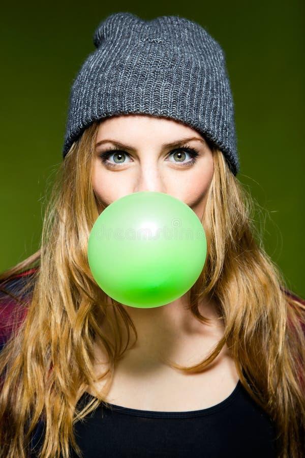 Belle jeune femme soufflant le bubblegum vert photographie stock libre de droits