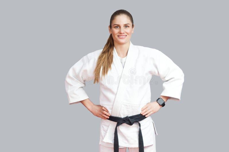 Belle jeune femme sportive blonde gaie heureuse dans le ki blanc images stock