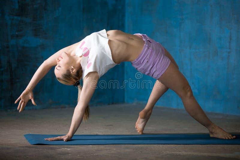 Belle jeune femme sportive faisant la posture de Camatkarasana image stock