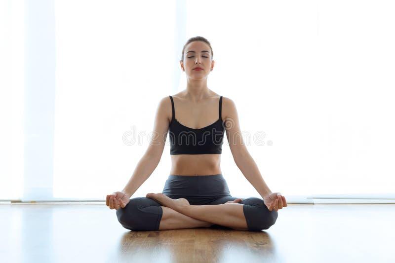 Belle jeune femme sportive faisant le yoga en position de lotus à la maison photo libre de droits