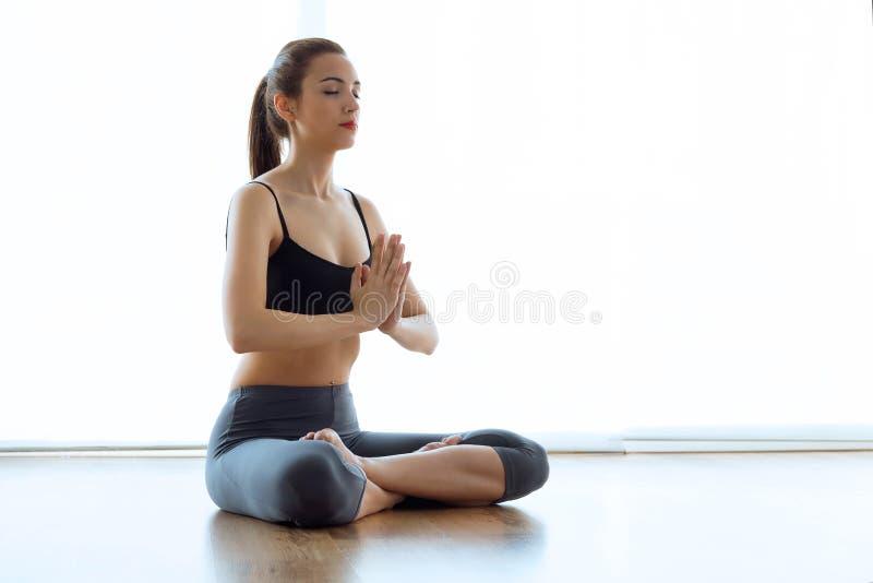 Belle jeune femme sportive faisant le yoga en position de lotus à la maison photos stock