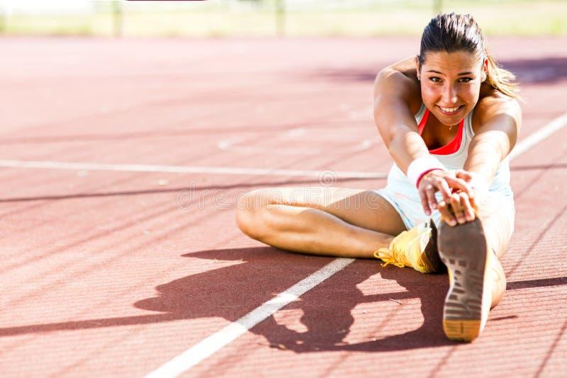 Belle jeune femme sportive s'étirant en été image stock