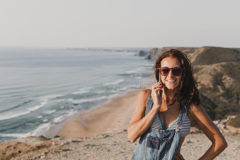 Belle jeune femme sur le dessus d'une colline parlant sur son téléphone portable et sourire Jeunes adultes lifestyle photographie stock libre de droits