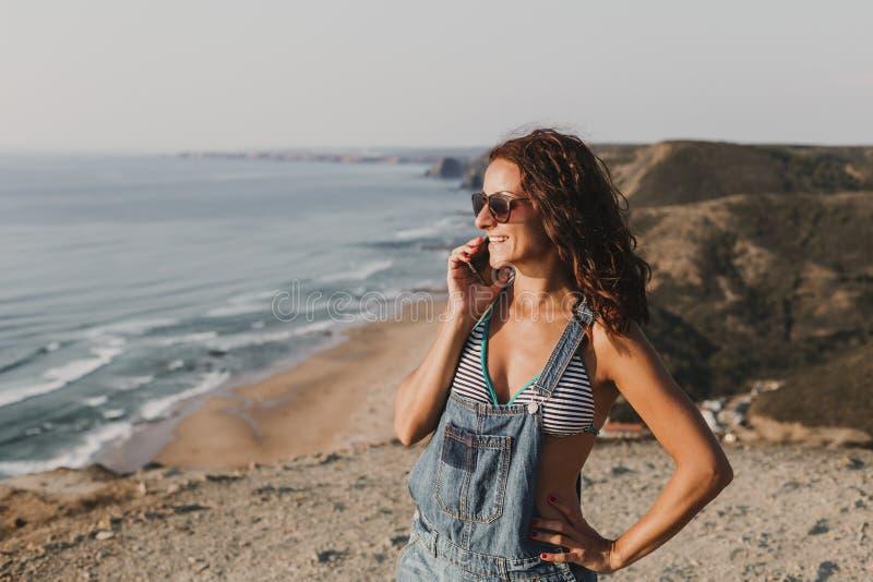 Belle jeune femme sur le dessus d'une colline parlant sur son t?l?phone portable et sourire Jeunes adultes lifestyle photo libre de droits