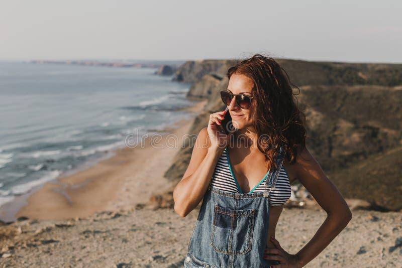 Belle jeune femme sur le dessus d'une colline parlant sur son t?l?phone portable et sourire Jeunes adultes lifestyle photos libres de droits
