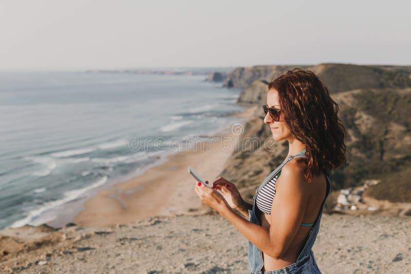 Belle jeune femme sur le dessus d'une colline utilisant son t?l?phone portable et sourire Jeunes adultes lifestyle photos libres de droits