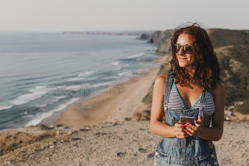 Belle jeune femme sur le dessus d'une colline utilisant son t?l?phone portable et sourire Jeunes adultes lifestyle image libre de droits