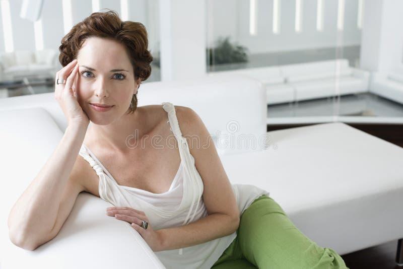Belle jeune femme sur Sofa In Living Room photographie stock libre de droits