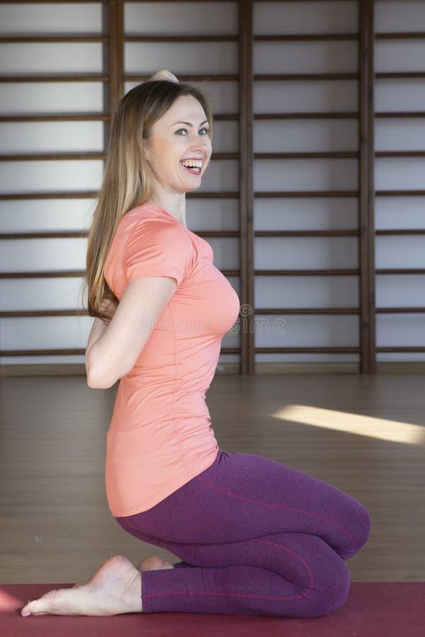 Belle jeune femme ?tablissant dans l'int?rieur de grenier, faisant l'exercice de yoga sur le tapis bleu, exercice d'?quilibre de  image stock