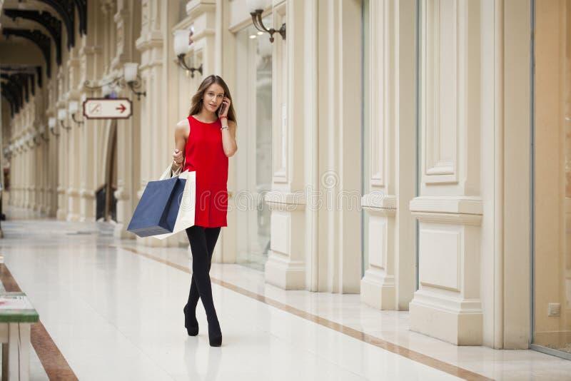 Belle jeune femme tenant des paniers marchant dans la boutique photos libres de droits