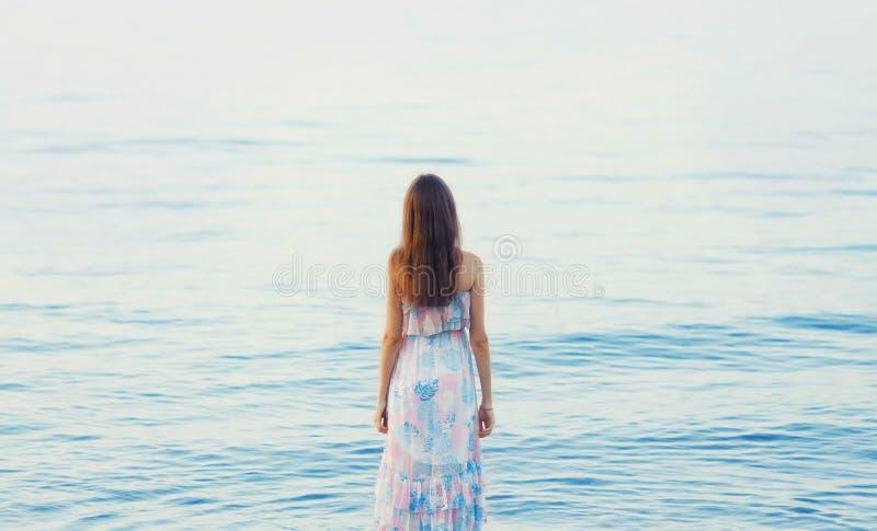 Belle jeune femme tenant la mer proche, femelle de dos images stock